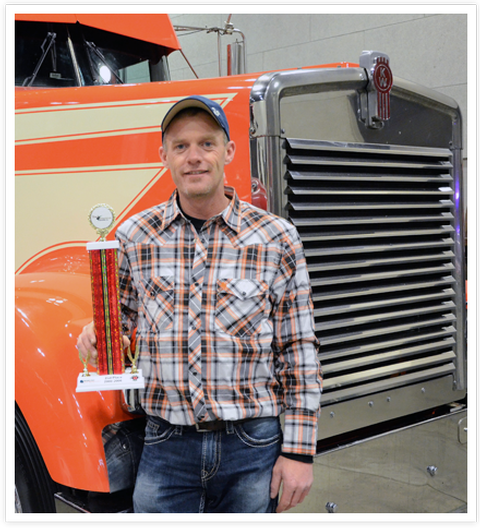 Picture of a guy holding a trophy after winning at the Mid-West Truck and Trailer Show